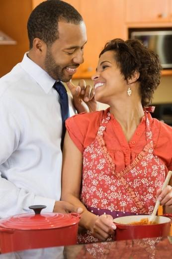 African American husband greeting wife in kitchen : Stock Photo