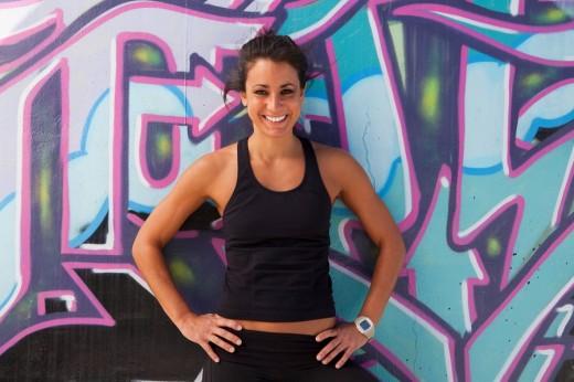 Active Cuban woman standing near graffiti on wall : Stock Photo
