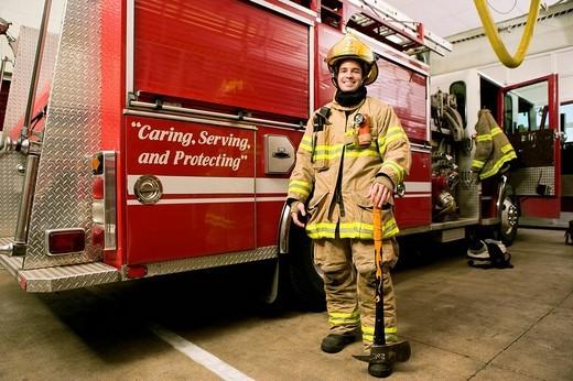 Hispanic fireman in coat and helmet : Stock Photo