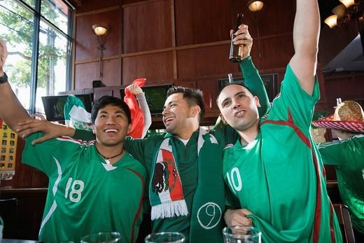 Cheering Hispanic men watching television in sports bar : Stock Photo