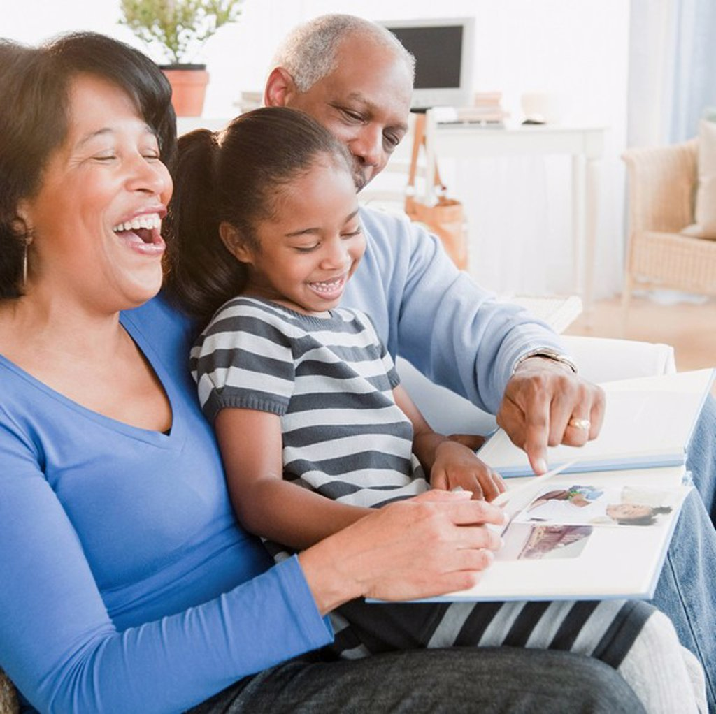Black grandparents looking at photographs with granddaughter : Stock Photo