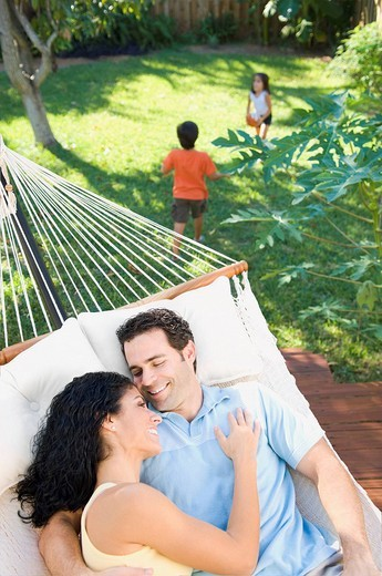 Couple relaxing in hammock with children playing in background : Stock Photo