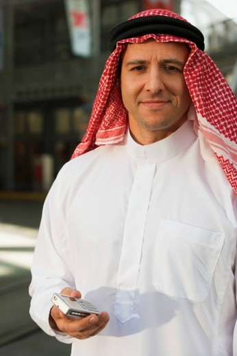 Middle Eastern man in traditional clothing with cell phone : Stock Photo