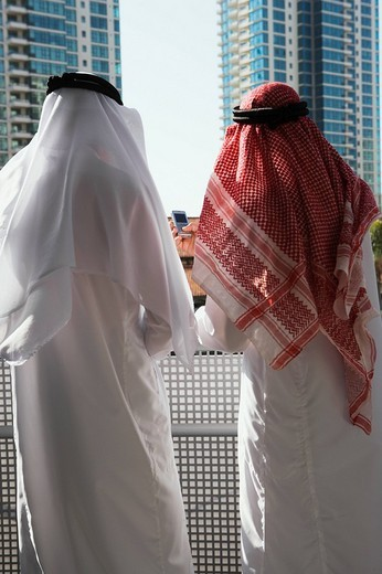 Middle Eastern man in traditional clothing looking at highrise : Stock Photo