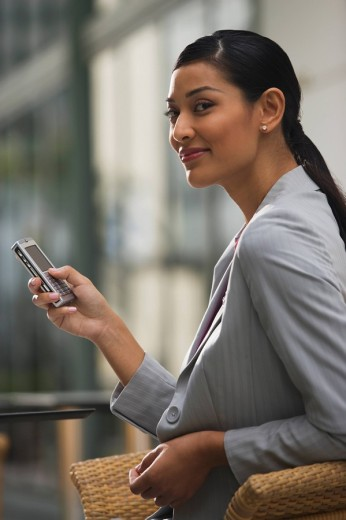 Pilipino businesswoman text messaging on cell phone : Stock Photo