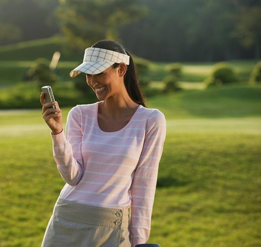 Pilipino golfer text messaging on cell phone : Stock Photo