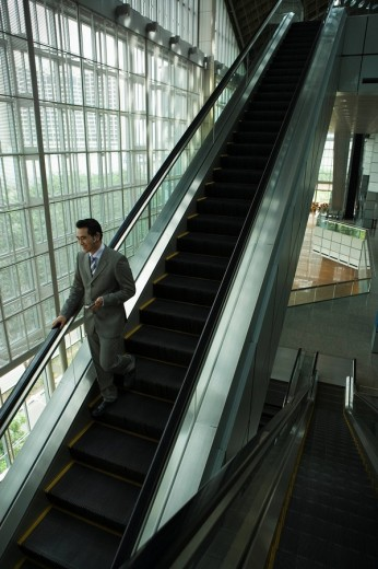 Chinese businessman holding cell phone on escalator : Stock Photo