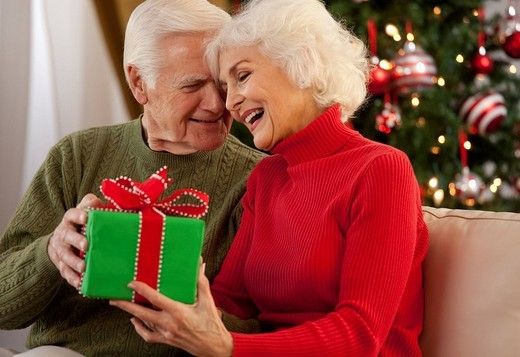 Caucasian man giving wife gift : Stock Photo