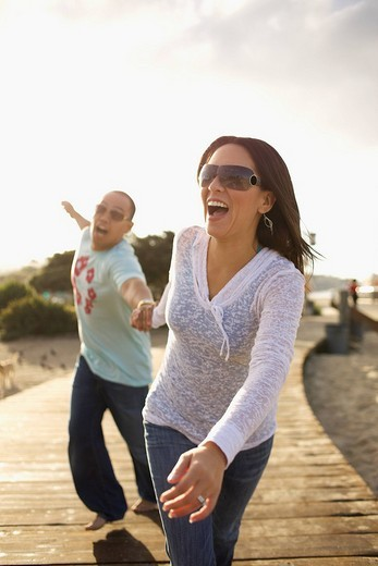 Couple holding hands and walking on boardwalk : Stock Photo