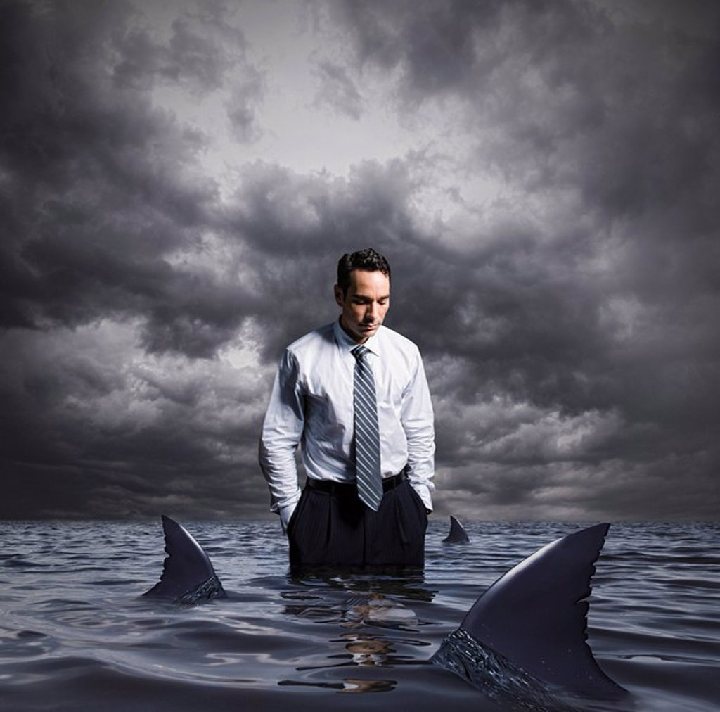Stock Photo: 1589-131414 Latin businessman standing in shark infested waters
