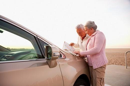 Senior Caucasian couple at beach looking at map : Stock Photo