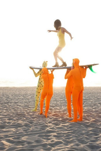 People dressed in strange costumes holding surfboard : Stock Photo