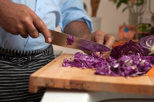 African American man cutting red cabbage : Stock Photo