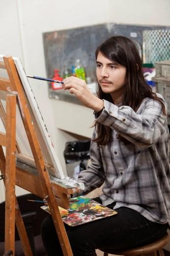 Hispanic student painting in art class : Stock Photo