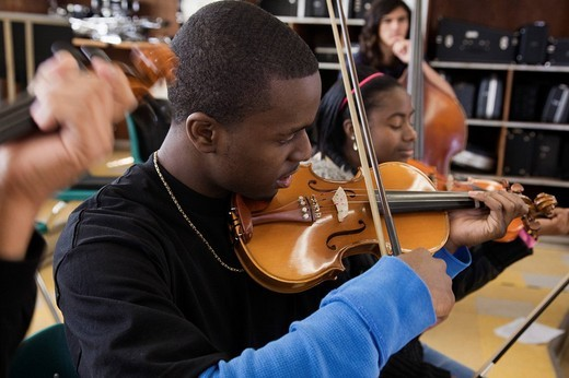 Students practicing in high school orchestra : Stock Photo