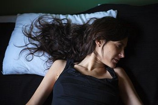Sad mixed race woman laying in bed : Stock Photo