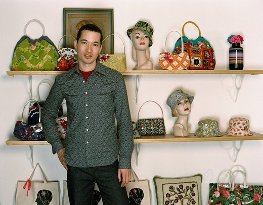 Mixed race man standing in retro purse shop : Stock Photo