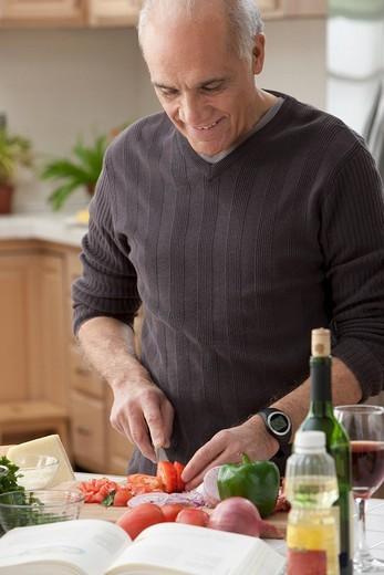 Hispanic man chopping vegetables in kitchen : Stock Photo