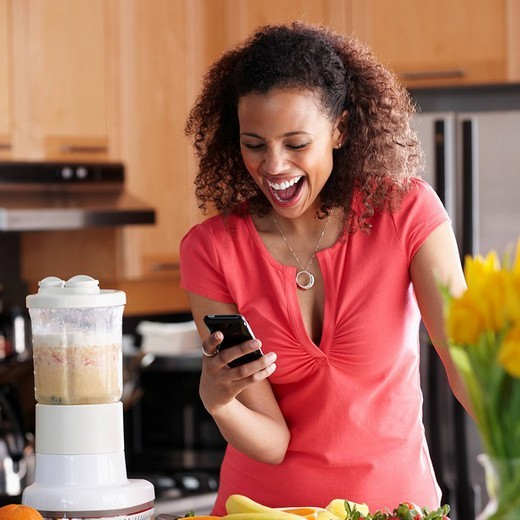 Black woman text messaging on cell phone in kitchen : Stock Photo
