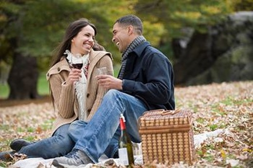 Couple drinking red wine in park : Stock Photo
