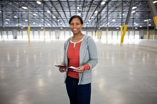 Black woman standing in empty warehouse : Stock Photo