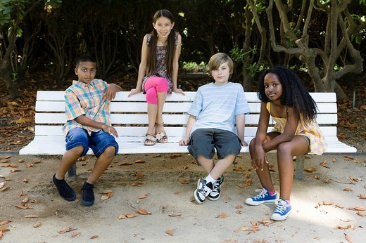 Children sitting on park bench : Stock Photo