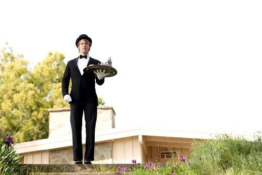 Caucasian man in tuxedo carrying tray : Stock Photo