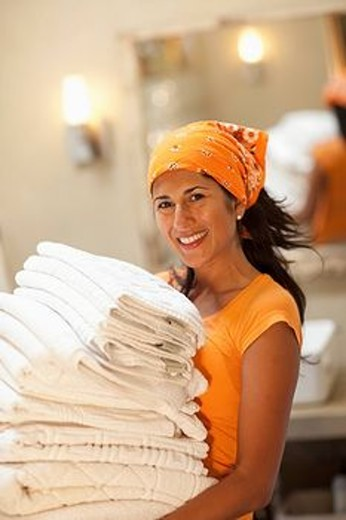Hispanic woman carrying stack of towels : Stock Photo