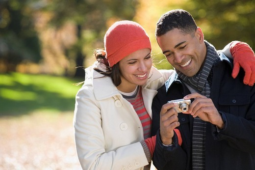 Couple looking at digital photographs on camera : Stock Photo