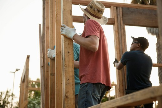 Construction workers adjusting house frame : Stock Photo