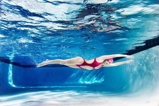 Caucasian woman swimming underwater : Stock Photo