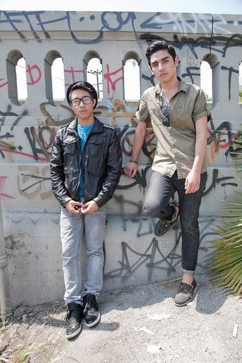 Serious teenage boys leaning against graffiti covered railing : Stock Photo