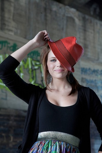 Smiling Caucasian teenage girl tipping hat on head : Stock Photo