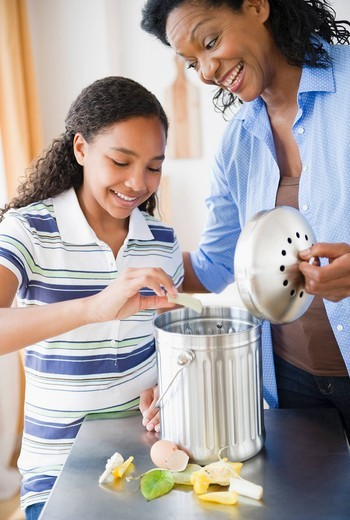 Mother and daughter composting together : Stock Photo