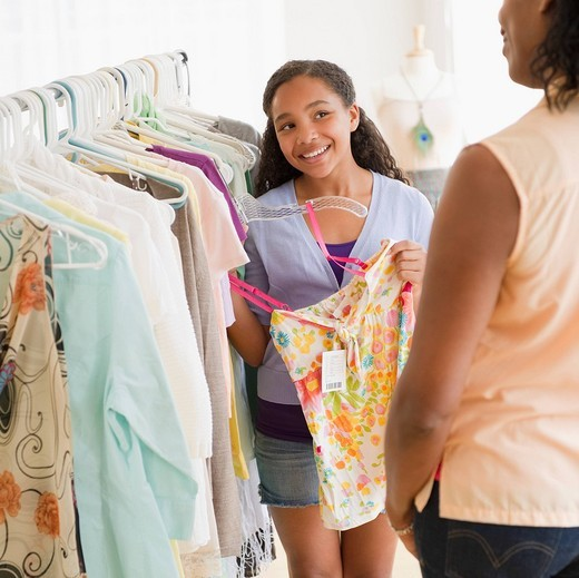 Mother and daughter shopping for clothing together : Stock Photo