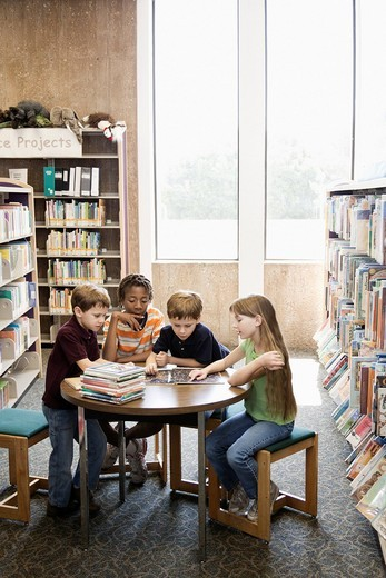 Children reading book together in library : Stock Photo