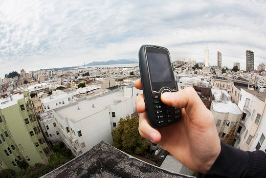 Caucasian man holding cell phone with cityscape in background : Stock Photo
