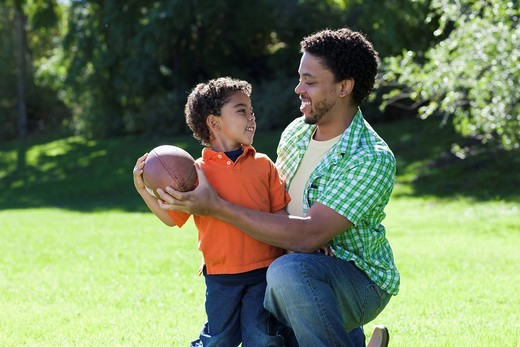 Father and son playing football : Stock Photo