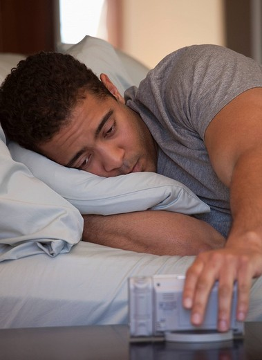 Mixed race man laying in bed checking the time : Stock Photo