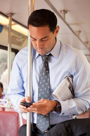 Hispanic commuter text messaging on bus : Stock Photo