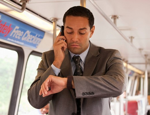 Hispanic commuter on bus checking the time : Stock Photo
