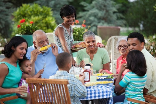 Multi_generation Black family eating at barbecue in back yard : Stock Photo