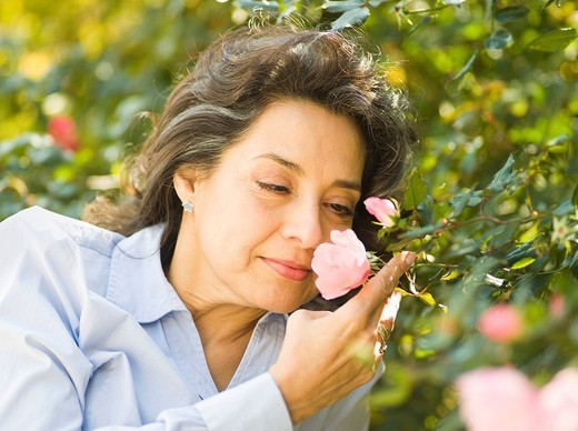 Caucasian woman smelling flower outdoors : Stock Photo