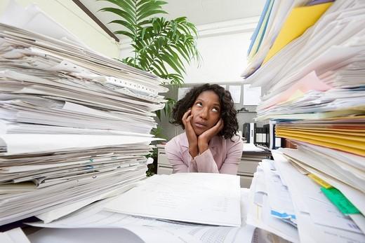 Black businesswoman between stacks of paperwork : Stock Photo