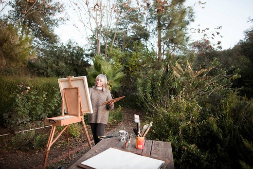 Caucasian woman painting on easel outdoors : Stock Photo