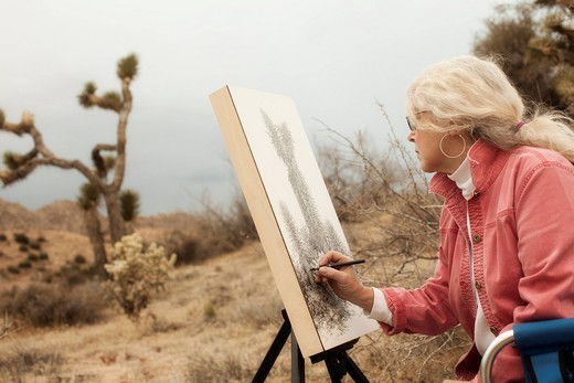 Caucasian woman drawing outdoors : Stock Photo