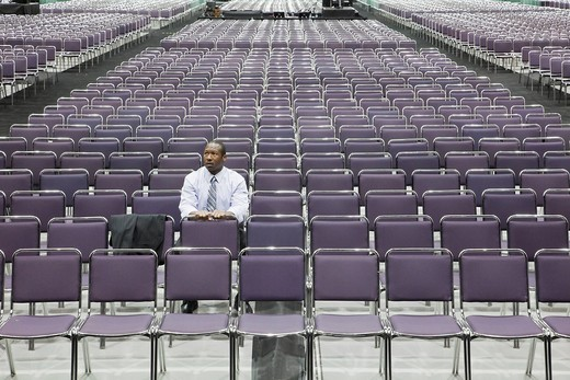Black businessman waiting in empty conference center : Stock Photo