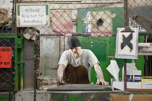Caucasian worker working in factory : Stock Photo