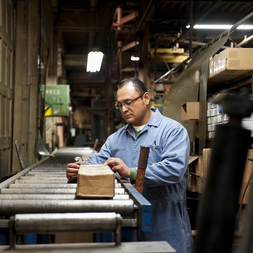 Mixed race worker looking at box in factory : Stock Photo