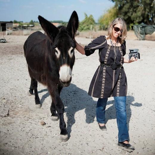 Caucasian woman walking with donkey : Stock Photo